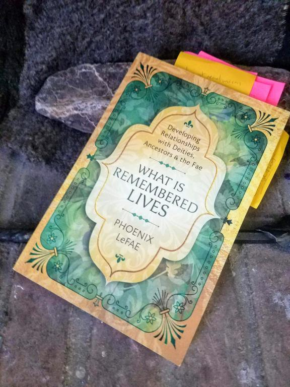A copy of What is Remembered Lives with a number of sticky notes as bookmarks, sitting on a stone hearth.