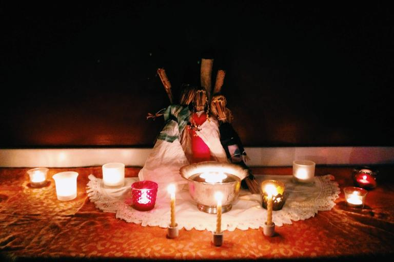 Many candles are lit around a silver bowl with more candles floating in it. Three rustic dolls are made of grass and linen.
