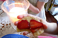 gluten-free animal cookies with sliced strawberries being held up by a child to the camera. A lit candle sits on the table which is covered with a lace tablecloth.