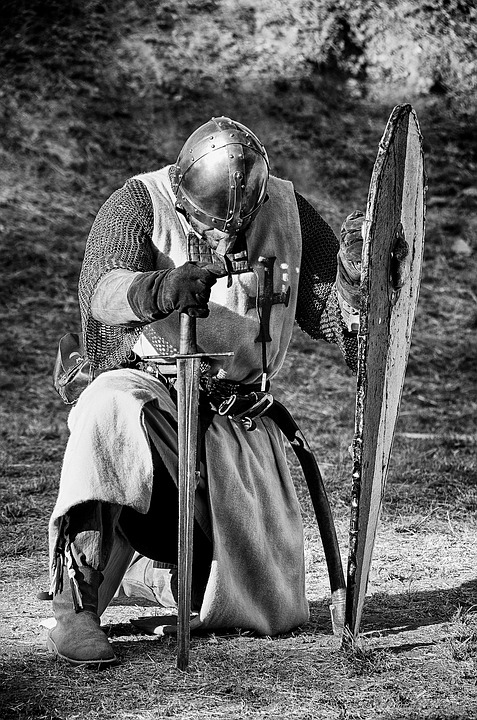 Picture of crusader with sword and shield, kneeling in prayer.