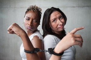 Two angry women connected by a pair of handcuffs