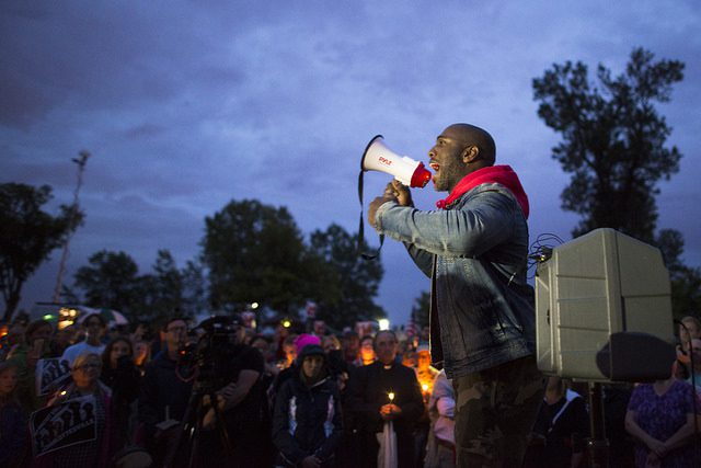 Speaker at vigil in Charlottesville following white nationalist rally. Photo by Fibonacci Blue. Some rights reserved. www.flickr.com