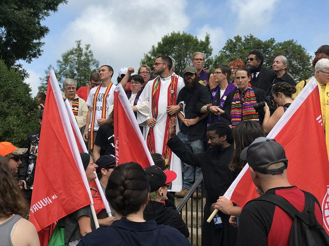 "Clergy at the stairs to Emancipation Park, resisting the ""Unite the Right"" rally in Charlottesville. Photo by Anthony Crider. Some rights reserved. Flickr.com"