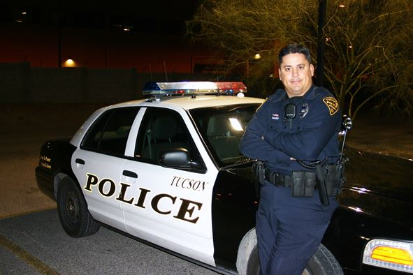 A police officer with his patrol car. Obtained through Creative Commons.
