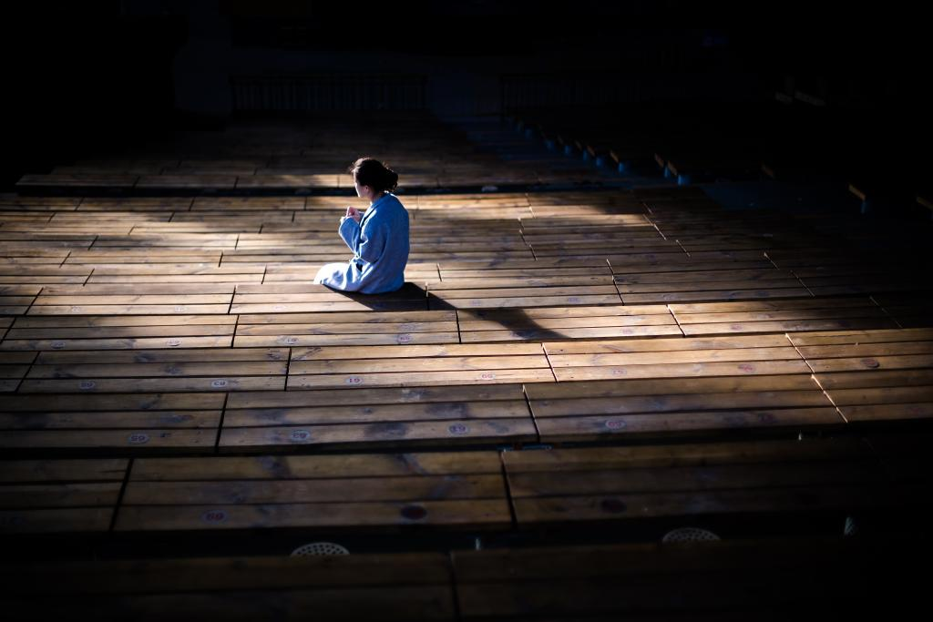 woman in prayer alone on large deck