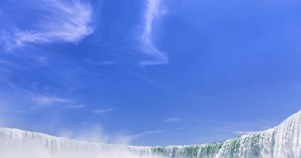 calm blue sky above raging waterfall