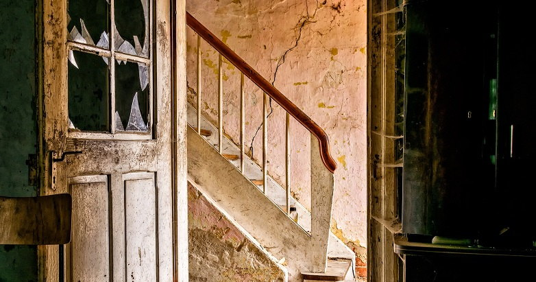 A color photograph of a staircase in a dilapidated house.