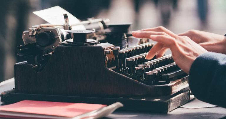 Photo of a person's hands typing on a manual typewriter.