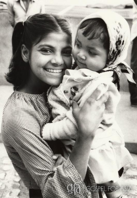 A young Southern Indian holds an orphan child who needs a remarkable mom - KP Yohannan - Gospel for Asia