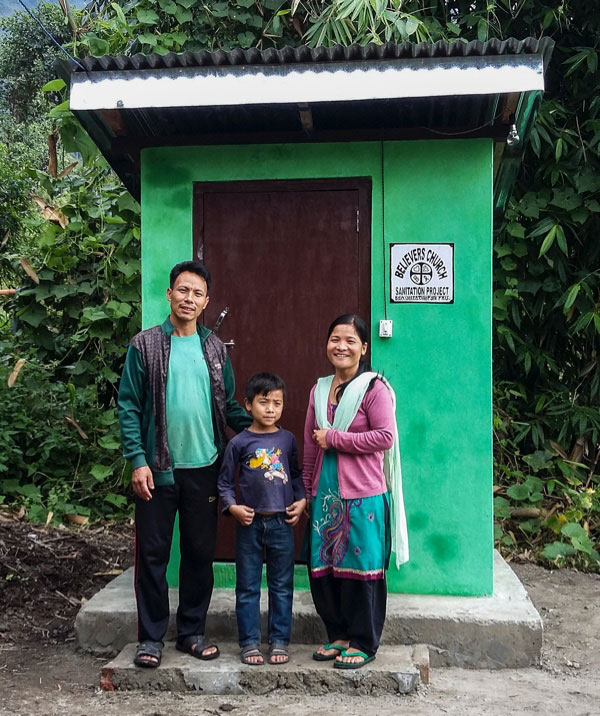 A family in front of a GFA-provided outdoor toilet and sanitation facility - KP Yohannan - Gospel for Asia