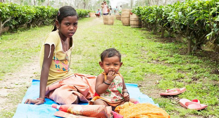 This girl takes care of her younger sister while her mother works at a tea plantation - KP Yohannan - Gospel for Asia
