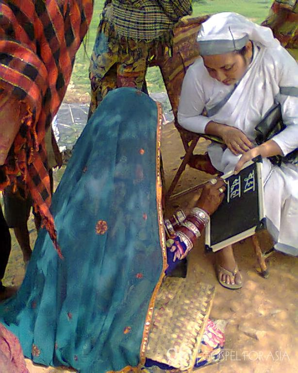 Habiba practices writing with Tamanna during literacy class.