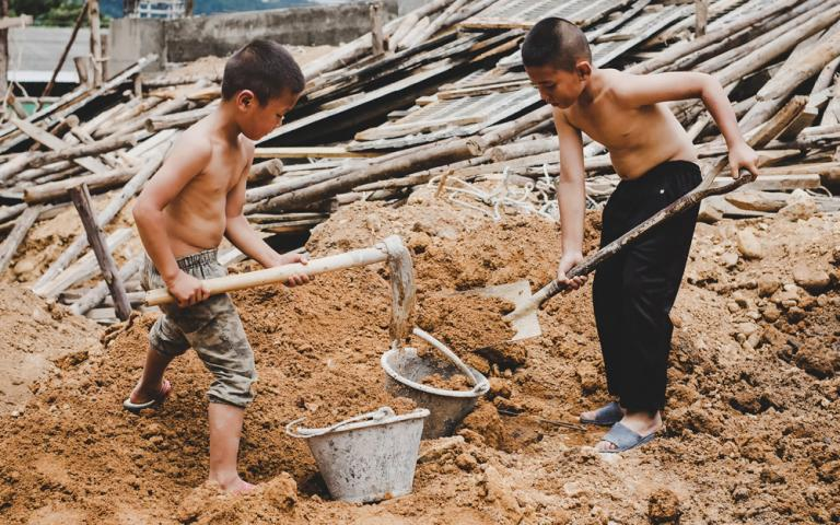 These young boys, deprived of their childhood and forced into child labor, are working hard on a commercial building structure.