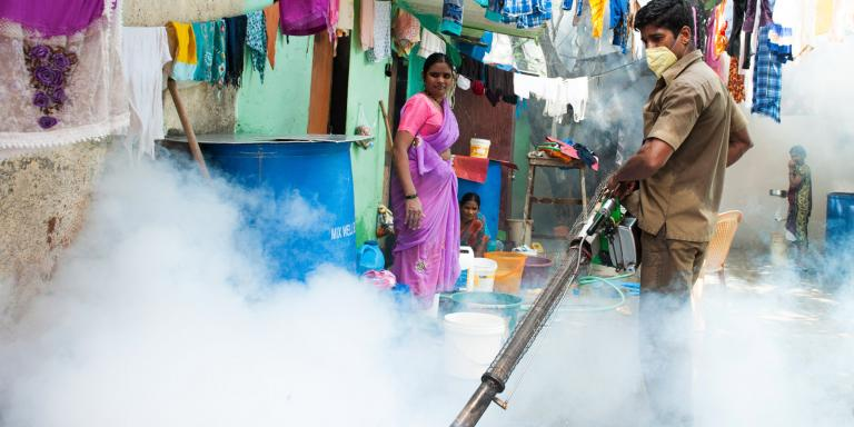 Gospel for Asia founded by Dr. KP Yohannan: The government working is spraying mosquito repelling smoke in a Mumbai slum to prevent malaria and other mosquito-spread diseases.