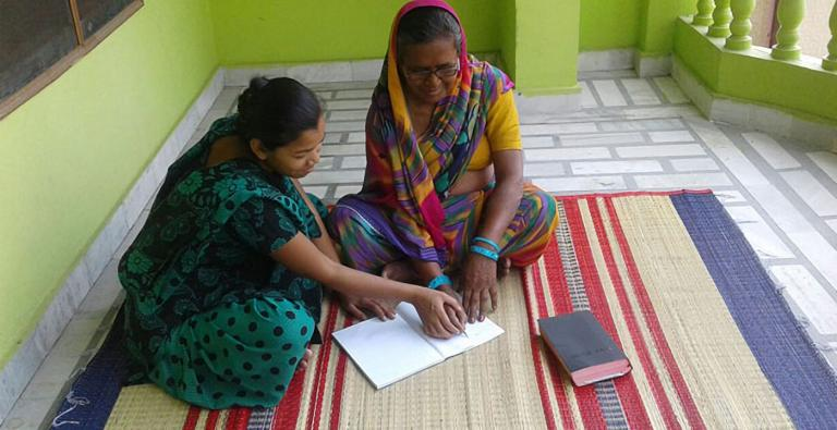 The joy of literacy - Gospel for Asia-supported women missionaries gently guided Jeni (right) as they taught her to read and write.