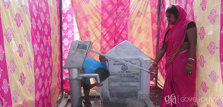 Gospel for Asia founded by Dr. K.P. Yohannan: A local woman pumps water for her daily use from the new well on the day it was dedicated. Her family is no longer threatened by waterborne illness that had been impacting her community.