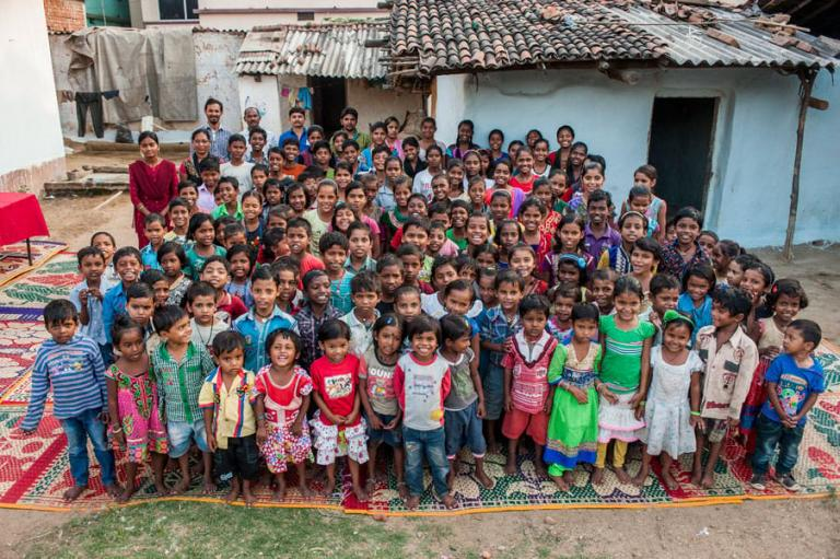 Children in Bridge of Hope center posing together with teachers