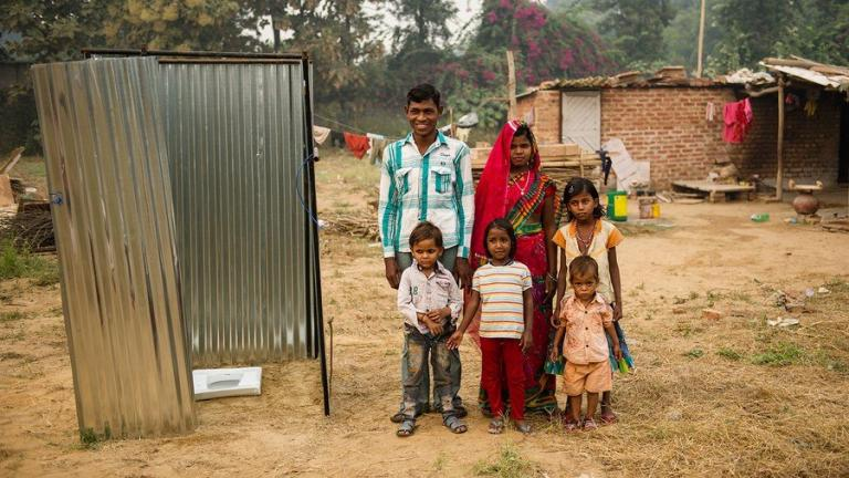 A family stands in front of a India toilet - a GFA-installed latrine or squatty potty.