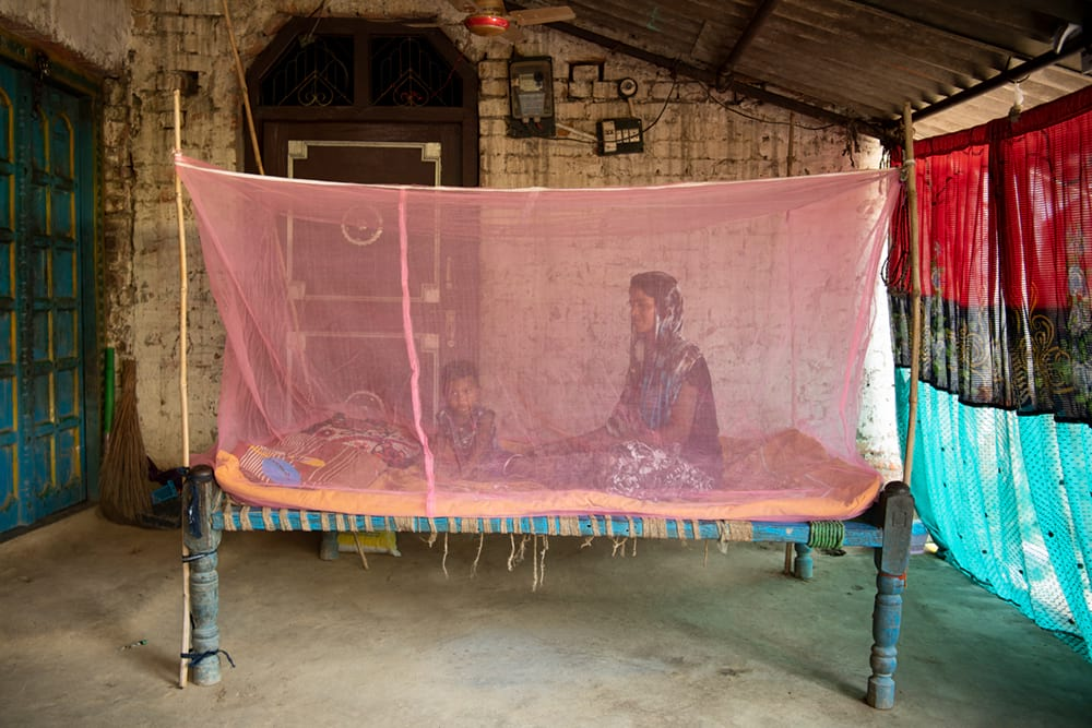 Mother and child resting inside their mosquito net