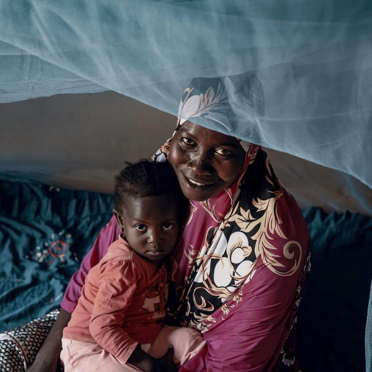 Mother and child under mosquito net