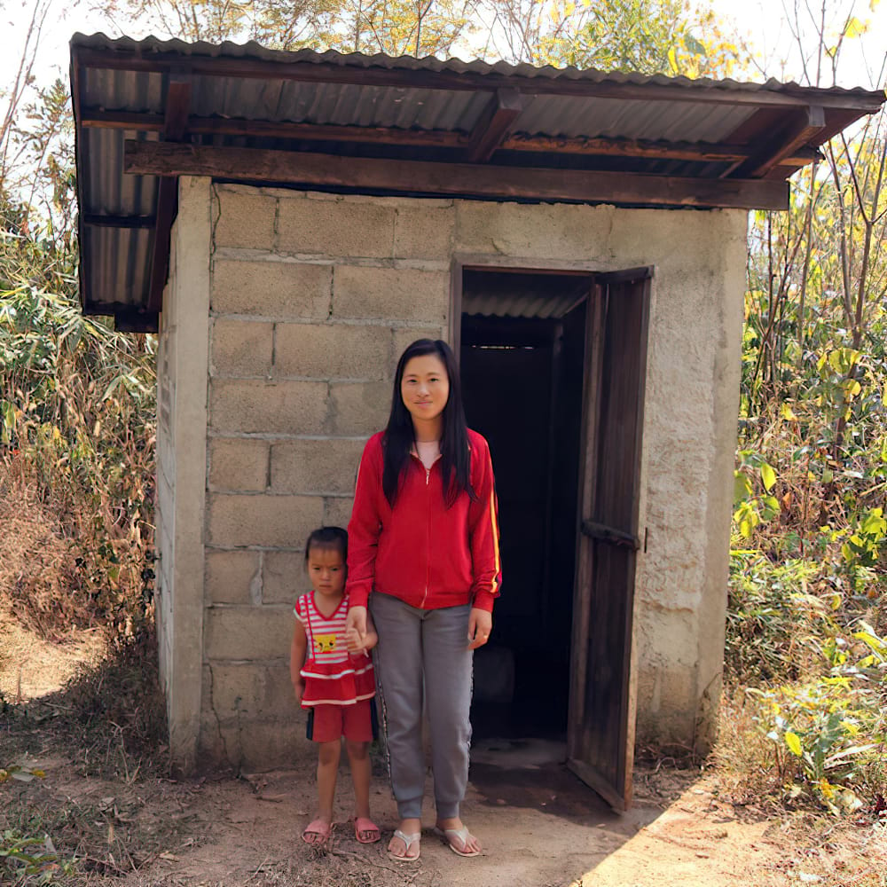 Woman and her child in Laos in front of an outdoor toilet