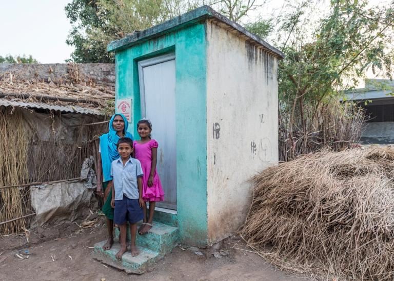 Mother and children outside outdoor toilet