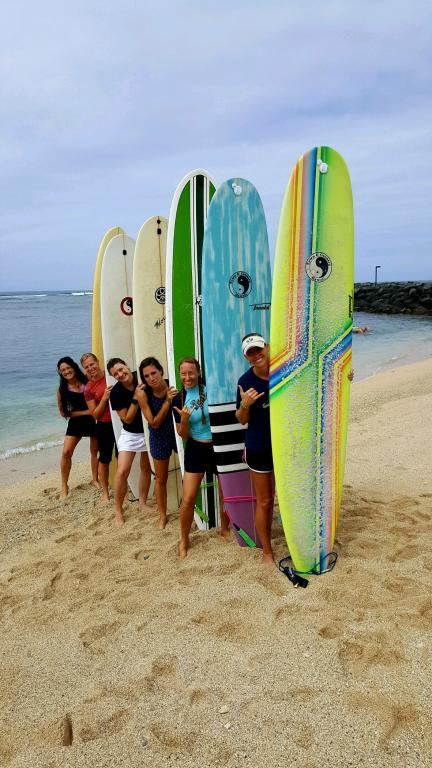 women holding surfboards at the beach