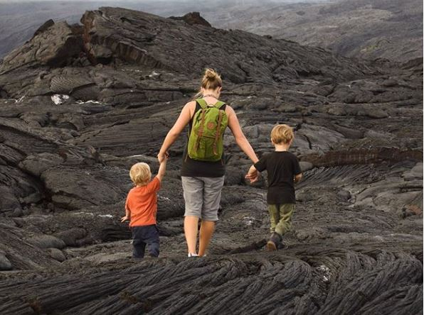 Mom and two boys walk across lava fields