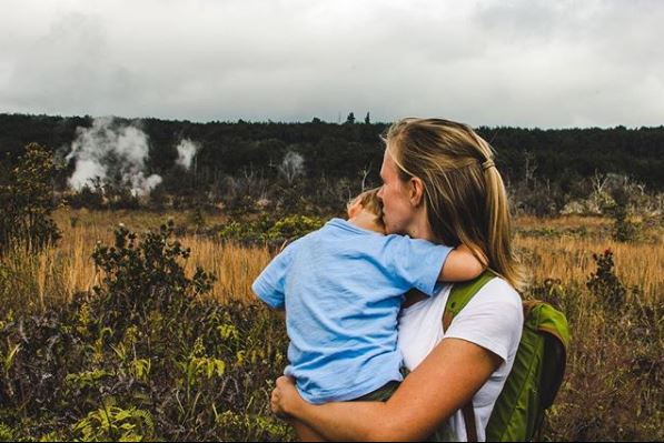 Mother and son watching volcanic steam rise from the scarred earth