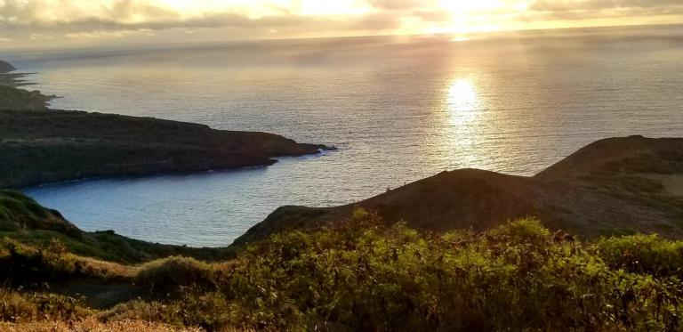 sunrise over bay, mountain, and ocean