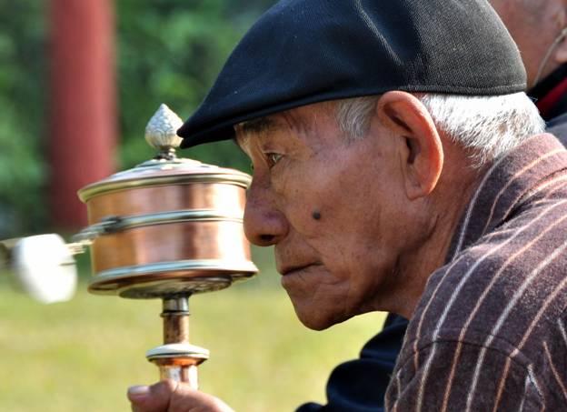 Tibetan man with a prayer wheel, Bodhgaya, India