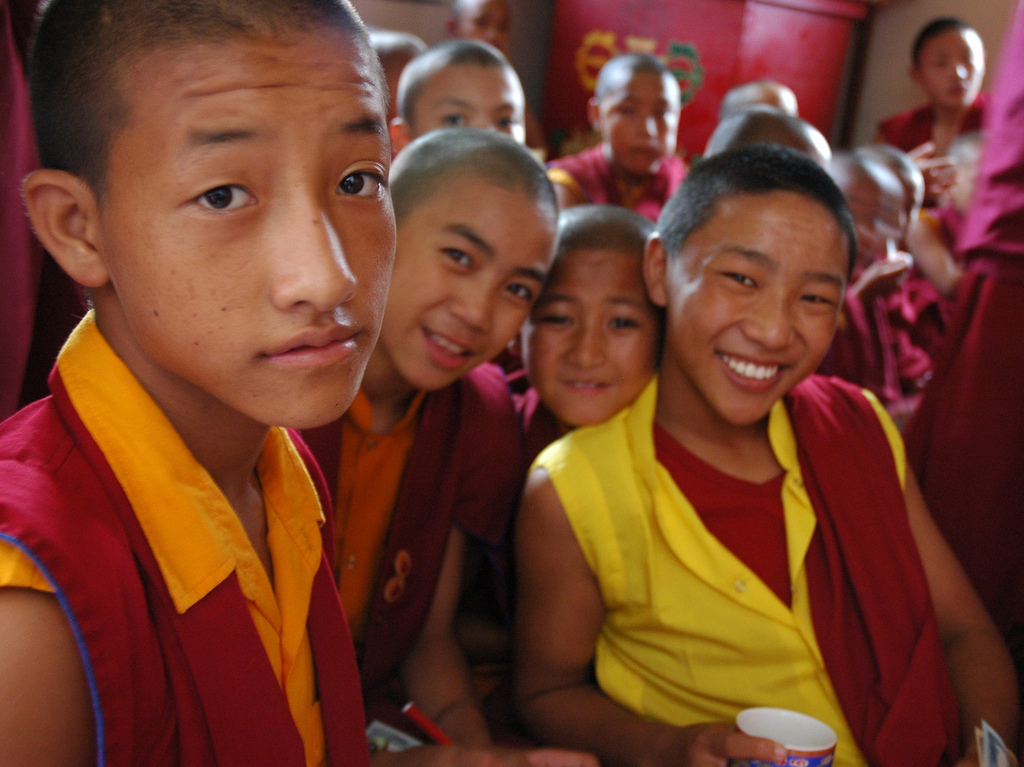 Young Tibetan boy monks in traditional robes, pose for a photo, tea break, Sakya Lamdre, side room, Tharlam Monastery of Tibetan Buddhism, Boudha, Kathmandu, Nepal (photo by flickr user Wonderlane, C.C.)