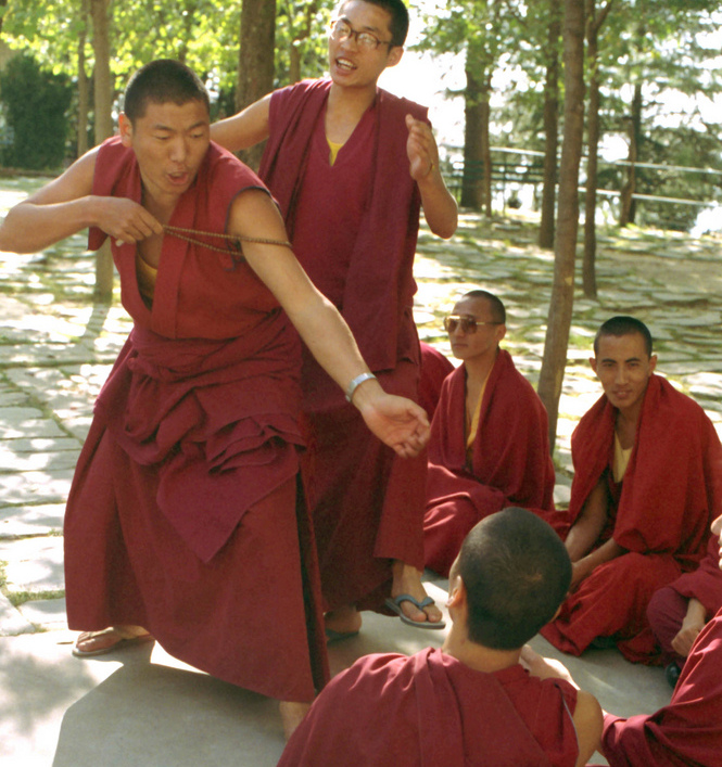 Maroon robed Tibetan Buddhist monks practicing philosophical debate, using the mala to illustrate a good point, coaching, argument, at His Holiness the 14th Dalai Lama's monastery in Dharamsala, India, on pilgrimage in 1992