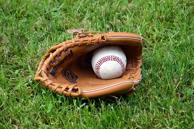 Baseball glove and ball on grass