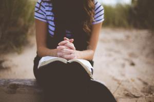 woman-black-white-stripe-t-shirt-book-her-lap-sitting-sand-daytime-82951113
