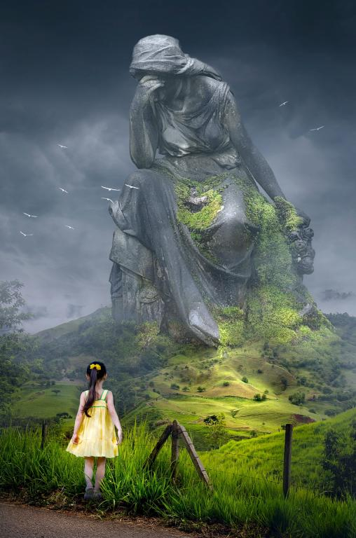 A little girl looking over at a huge monument statue of a weeping lady