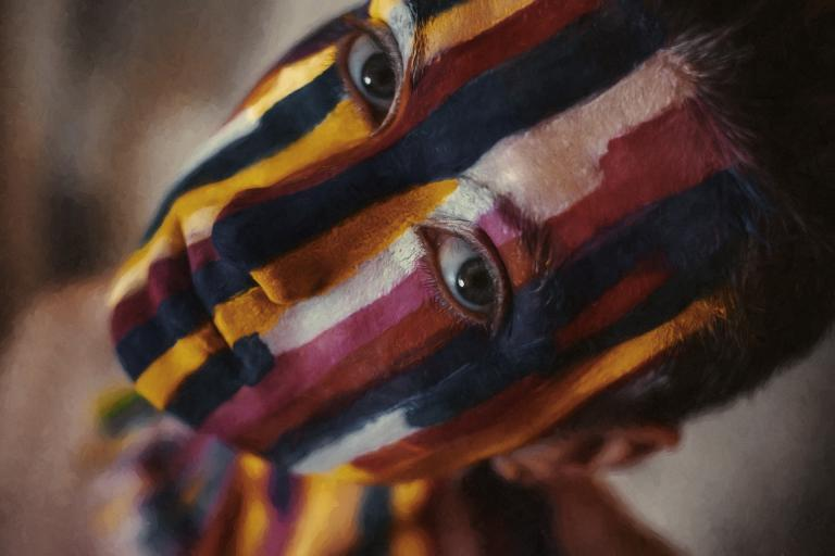 a woman looking up into the camera, her face painted in vertical lines of dark red, yellow, white and black.