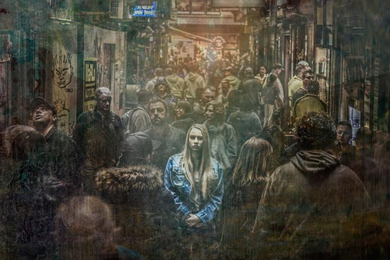 a girl in a blue jacket stands in the middle of a crowded train, but everything else is grungy shades of brown; an image of isolation