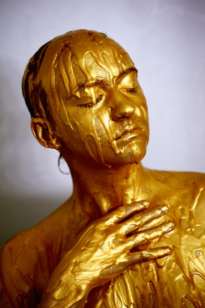 A woman drenched in gold paint, like a melting statue