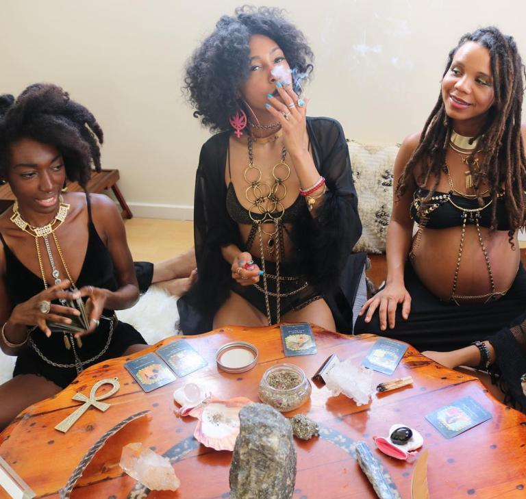 three awesome black witches around a table full of crystals and tarot