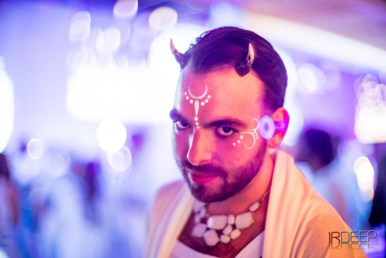a male witch with small satyr horns, white paint design on his brow, and beautifully layered pink and blue lighting