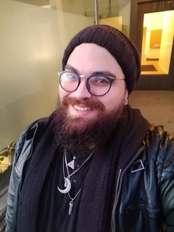 a bearded witch with round glasses and a big smile