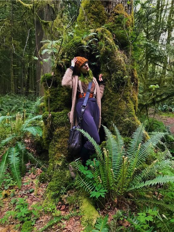 a pale witch in bohemian clothing standing n the hollow of a mossy green tree