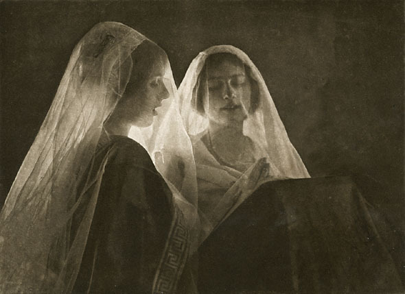 two white women standing close to one another, each veiled