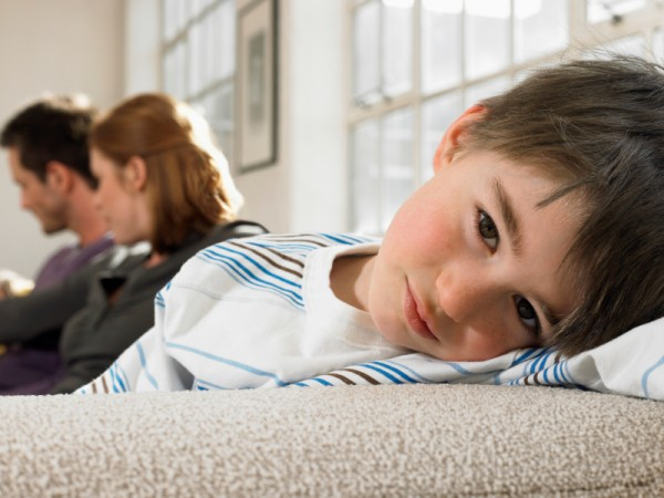Boy Relaxing On Sofa With Parents In Background
