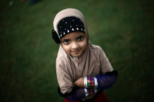 Indian girl poses, as she attends the Eid prayers in Delhi, India. Image by Adnan Abidi/Reuters