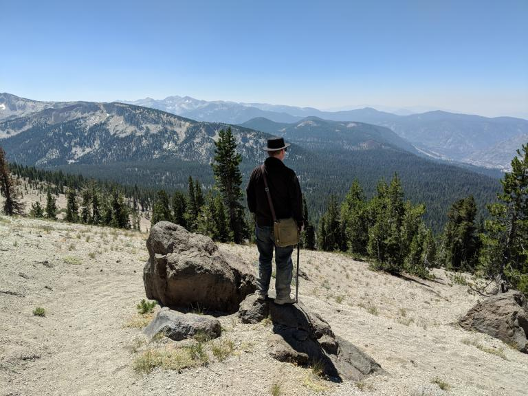 A man in a hat, with a cane, facing a distant mountain range.