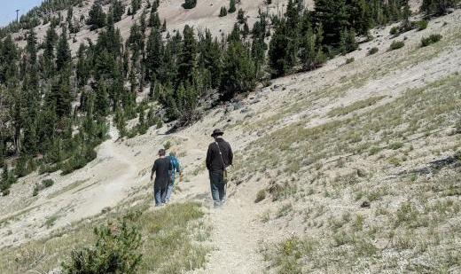 Three figures on a mountainside, following a dusty path.