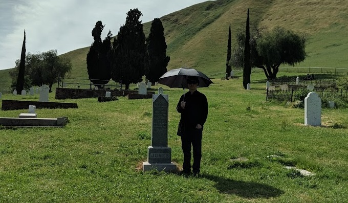 A man stands next to a grave with an umbrella protecting him from the glaring sun.