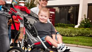 Happy boy with Down syndrome in stroller